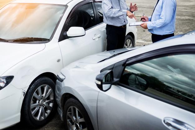 agente-seguros-que-escribe-tablero-mientras-que-examina-coche-despues-accidente_1423-1729